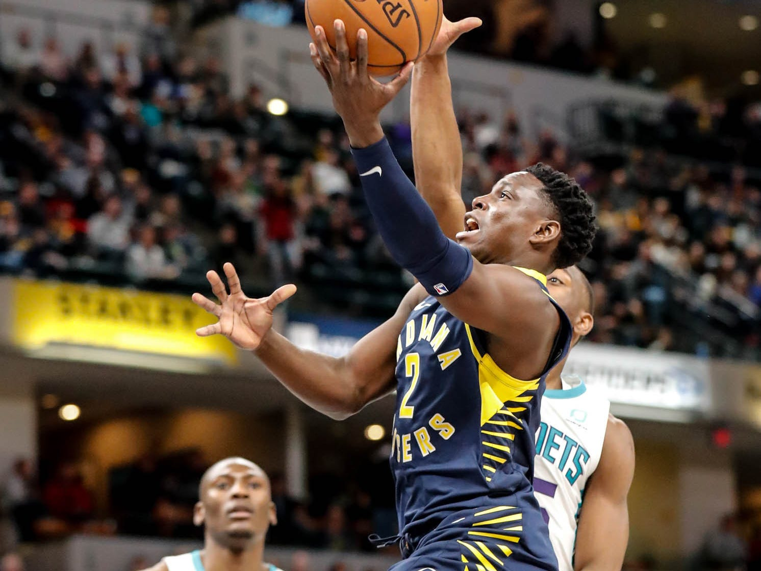 Indiana Pacers guard Victor Oladipo (4) shoots a layup past Charlotte Hornets forward Nicolas Batum (5), and Charlotte Hornets center Bismack Biyombo (8), during a game between the Pacers and Hornets at Bankers Life Fieldhouse on Sunday, Jan. 20, 2019.
