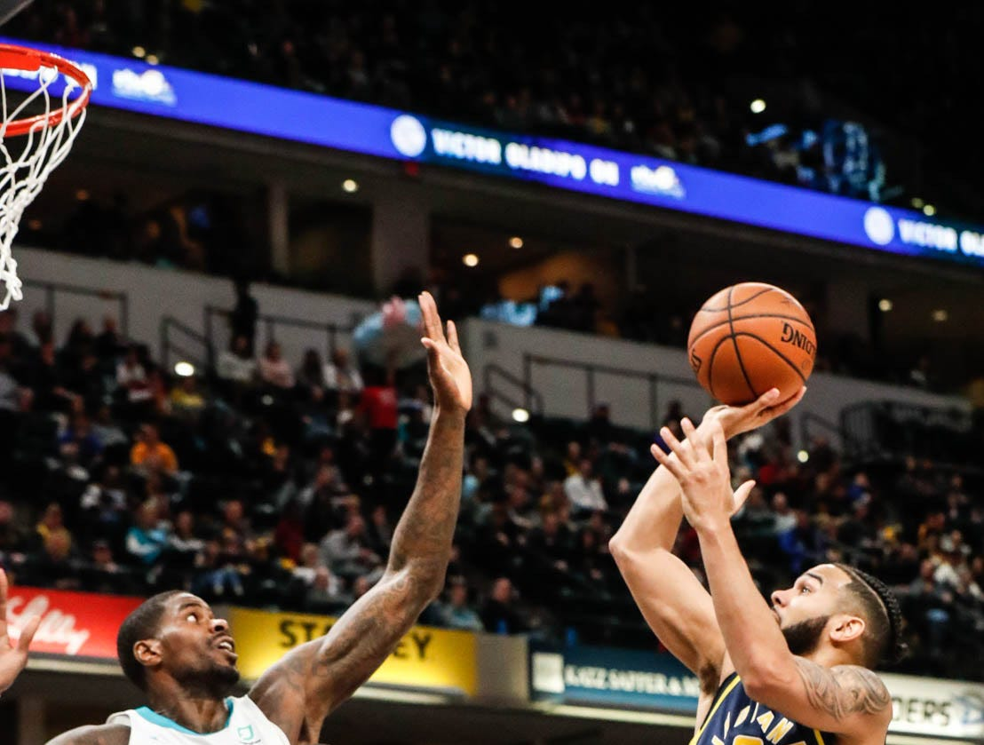 Indiana Pacers guard Cory Joseph (6), shoots over Charlotte Hornets center Bismack Biyombo (8), and Charlotte Hornets forward Marvin Williams (2), during a game between the Pacers and Hornets at Bankers Life Fieldhouse on Sunday, Jan. 20, 2019.