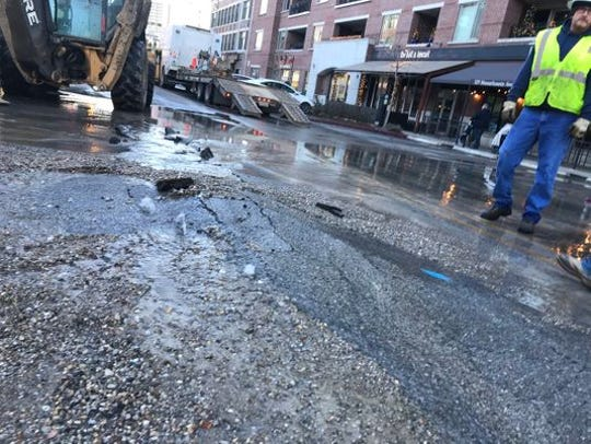 Citizens Energy crews try to repair damage from a water main break in the 300 block of Massachusetts Avenue in December 2018.