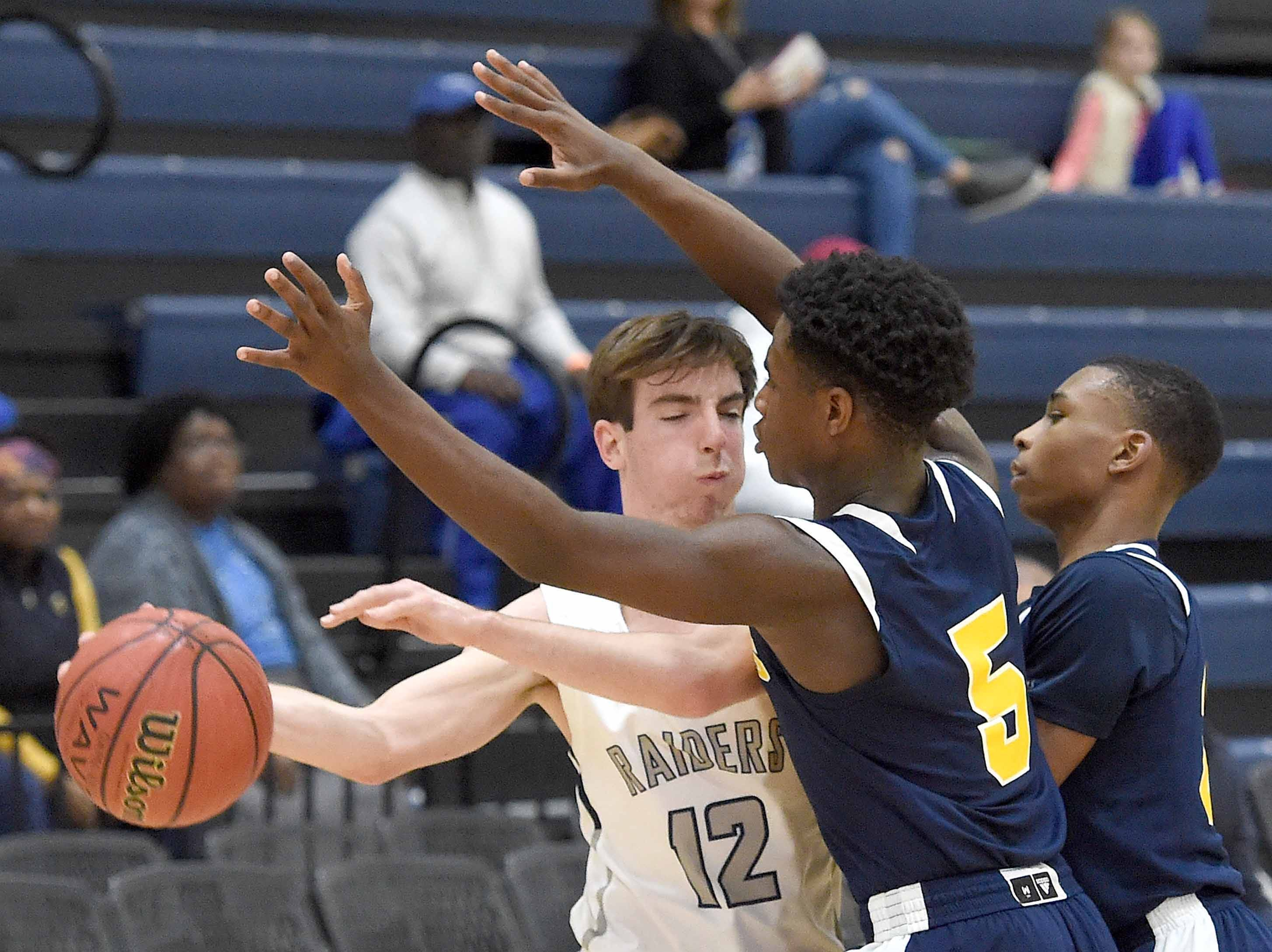 Jackson Academy's Will Travelstead (12) tries to beat a St. Joseph double team of Nathan Nickens (5) and Douglas Watson on Monday, January 21, 2019, at the Rumble in the South high school basketball tournament at St. Andrew's Episcopal School in Ridgeland, Miss.