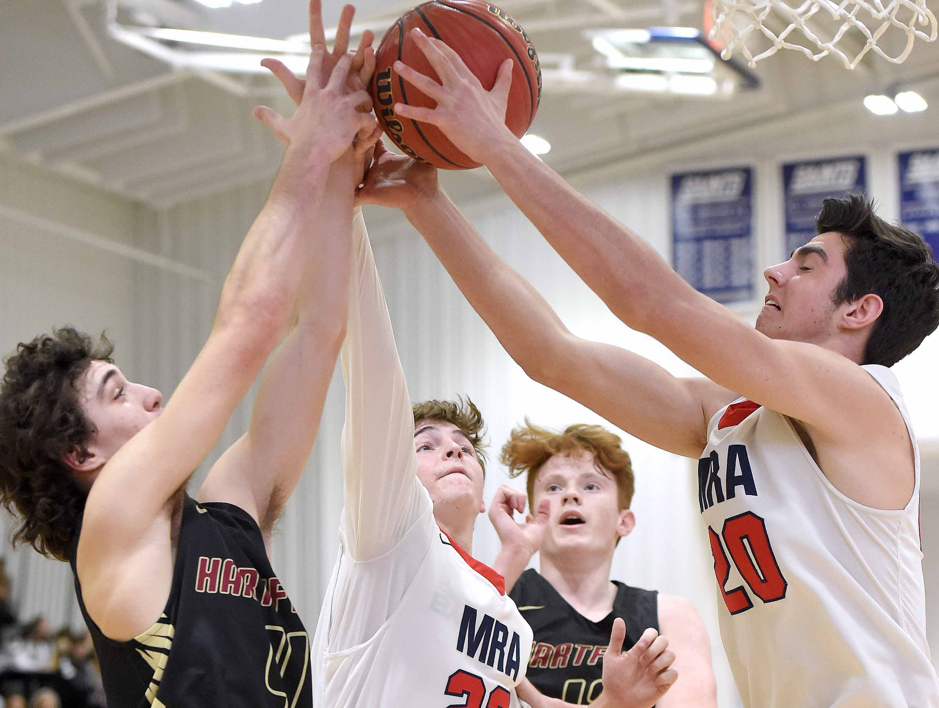 Hartfield's Will Sullivan (4) and Shane Wingate (second from right) fight for a rebound with MRA's Hamp Hudnall (22) and Russ Sceroler (20) on Monday, January 21, 2019, at the Rumble in the South high school basketball tournament at St. Andrew's Episcopal School in Ridgeland, Miss.