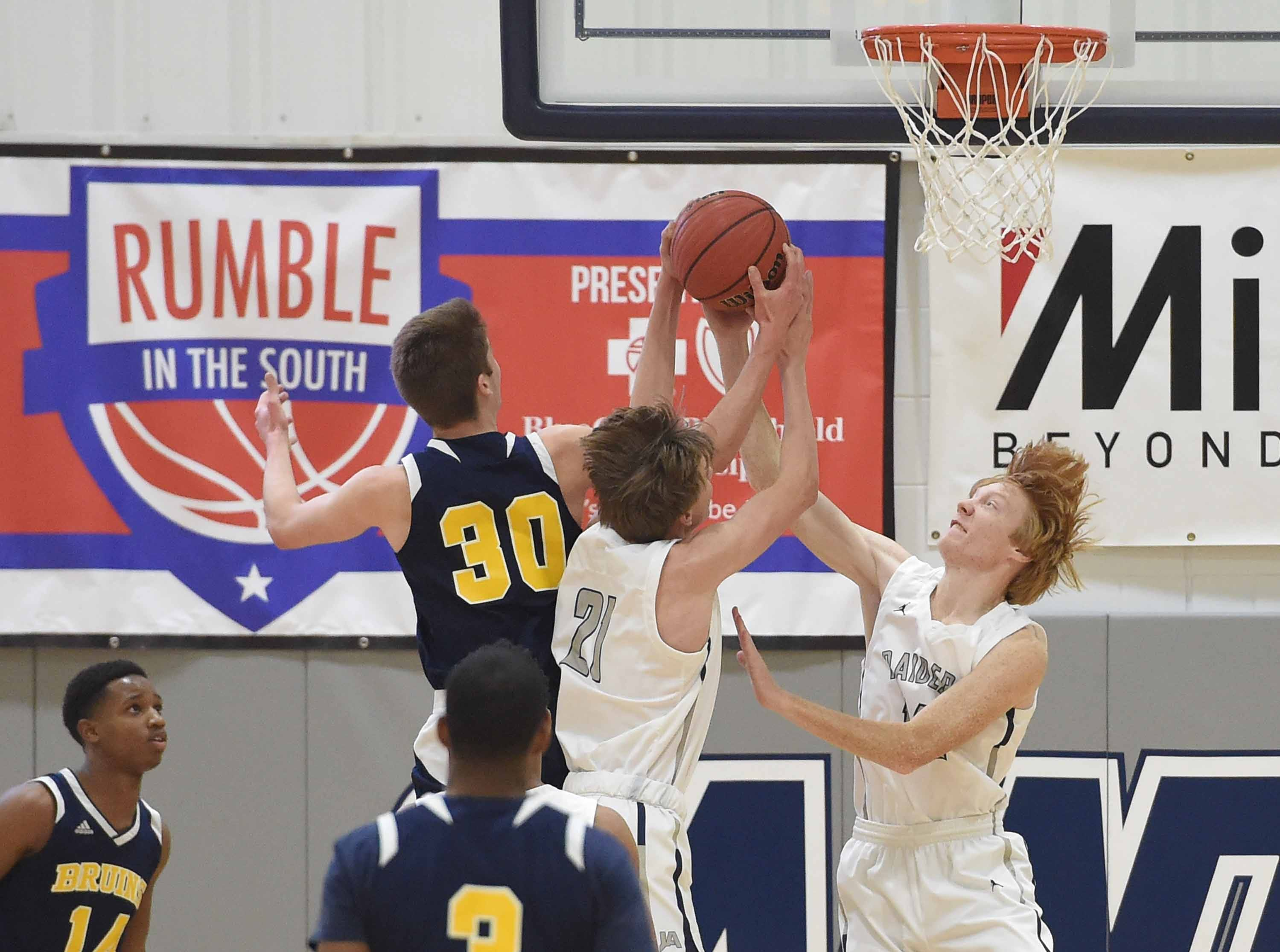 St. Joseph's Grayson Foley (30) battles for a rebound with Jackson Academy's Jonathan Lucas (21) and Tanner Robertson (14) on Monday, January 21, 2019, at the Rumble in the South high school basketball tournament at St. Andrew's Episcopal School in Ridgeland, Miss.