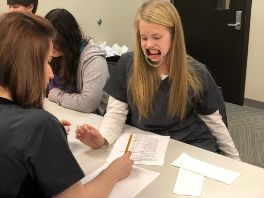 Katie Grace McSwain, a junior at Hardin County High School, wears a mouth brace to mimic the difficulty a patient has speaking after having a stroke. McSwain tries to read the paper to Pichabo Wilbanks, a senior at Hardin County High School at the stroke communication station for Nursing Day at the UT Martin Parsons Center. Carlee Rogers, a junior at Riverside High School, said the stroke communication station was her favorite part of Nursing Day.
