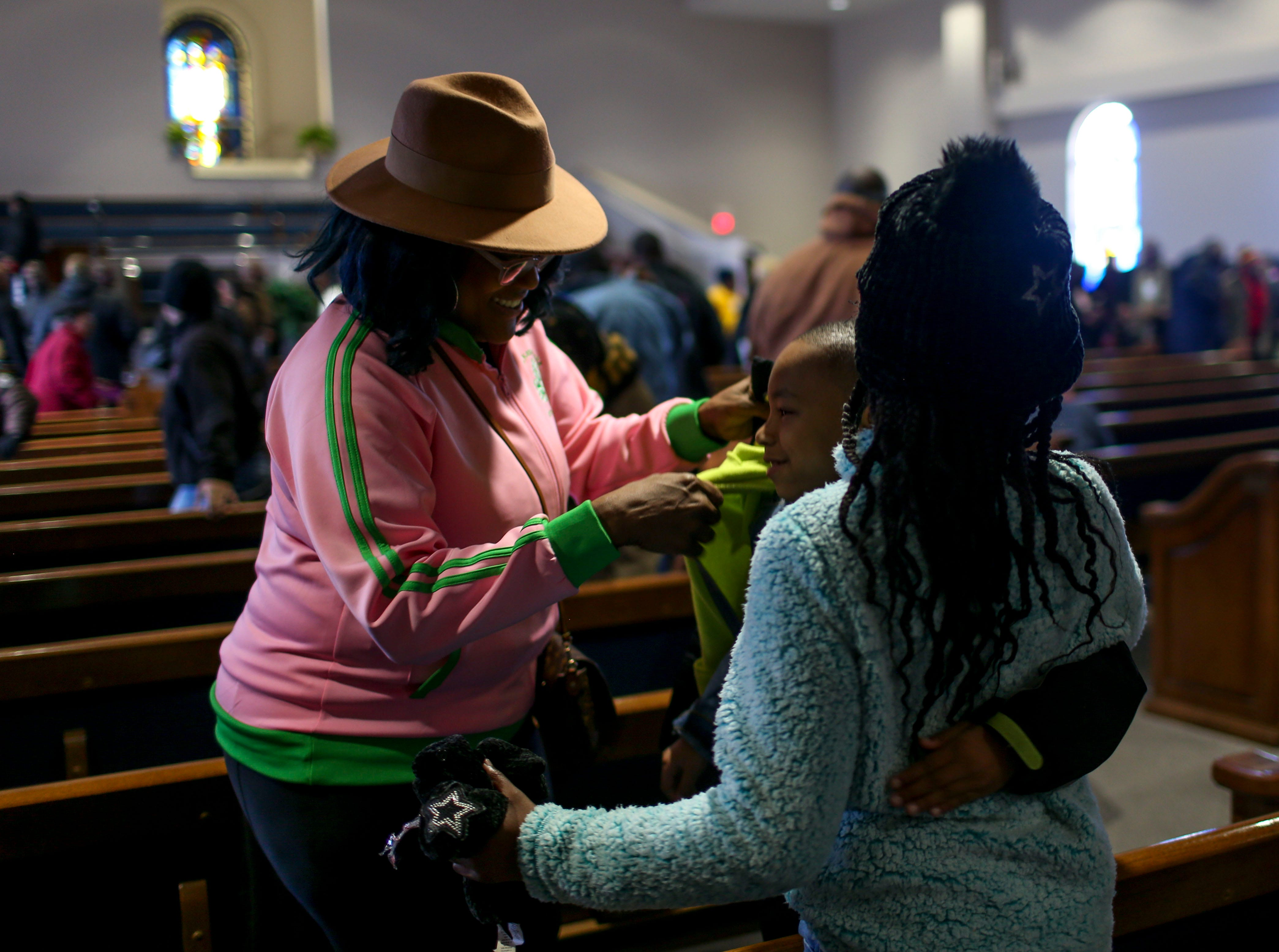 Teri Wood, left, tries to help put a coat on Corinthian Wood, 6, center, who's busy hugging Jamiya Armstrong, 11, right, during a service held for Martin Luther King Jr. Day at Mt. Zion Baptist Church in Jackson, Tenn., on Monday, Jan. 21, 2019.