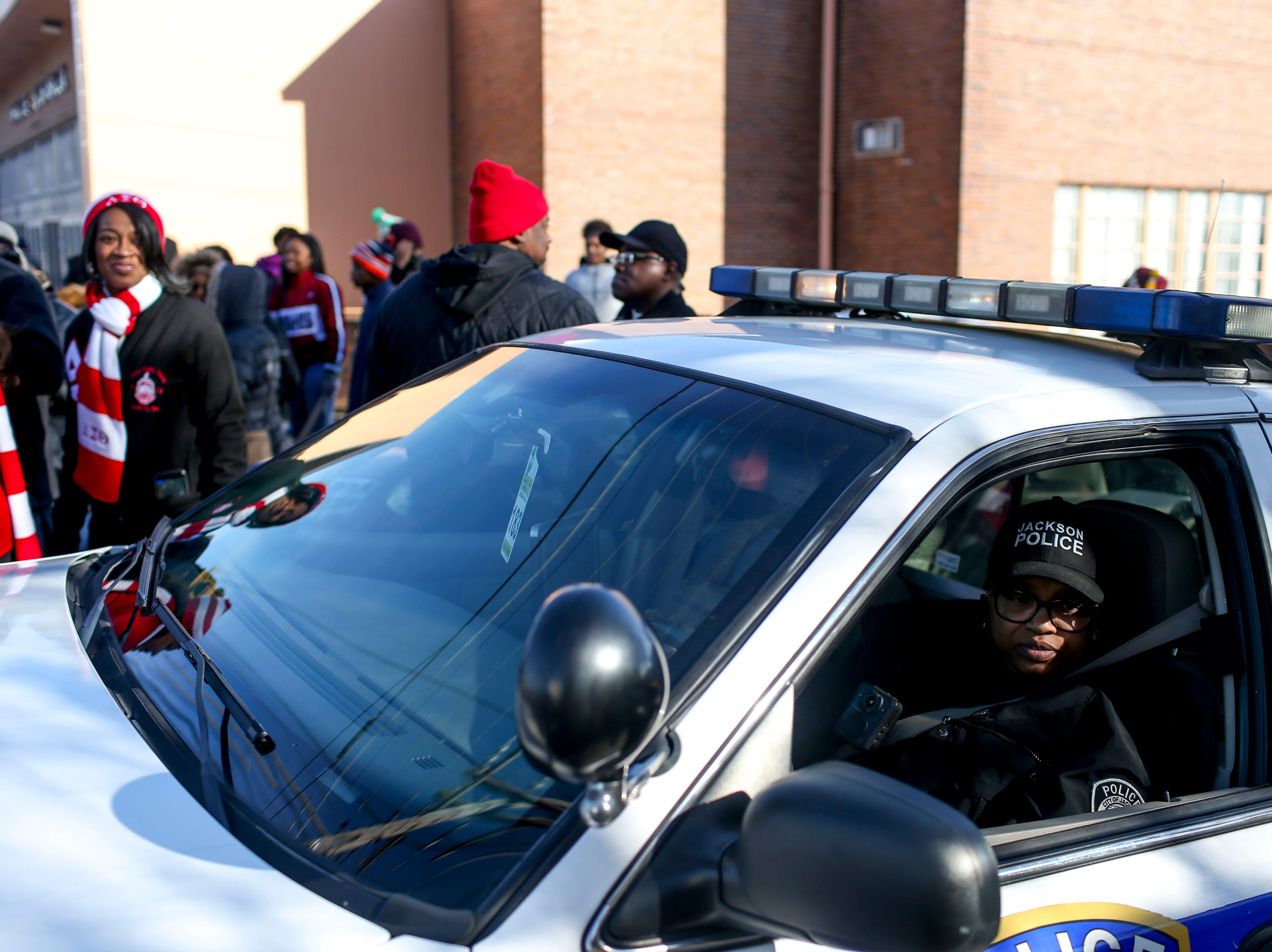 A Jackson Police officer looks out of their cruiser window before leading a march through downtown Jackson to Mt. Zion Baptist Church at T.R. White Sportsplex in Jackson, Tenn., on Monday, Jan. 21, 2019.