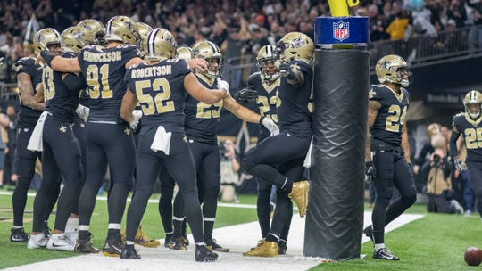 The Saints defense celebrates in the end zone during Sunday's NFC Championship in New Orleans.