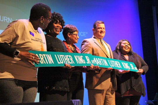 Marion Mayor Scott Schertzer showcases prototypes of new street signs that will replace those that say Cass Avenue. He was joined by Aurea Deas, right, who grew up around Cass Avenue and nearby Martin Luther King Jr. Park.