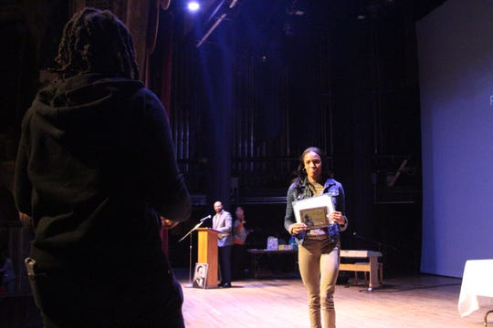 Rebekka Twine, a junior at Pleasant High School, walks off the stage on Monday with a plaque she earned for winning first place in a speech contest earlier this month. Students were tasked with talking about the importance of King's message of peace, freedom and equality.