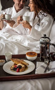 A couple enjoys breakfast in bed at the Delafield Hotel