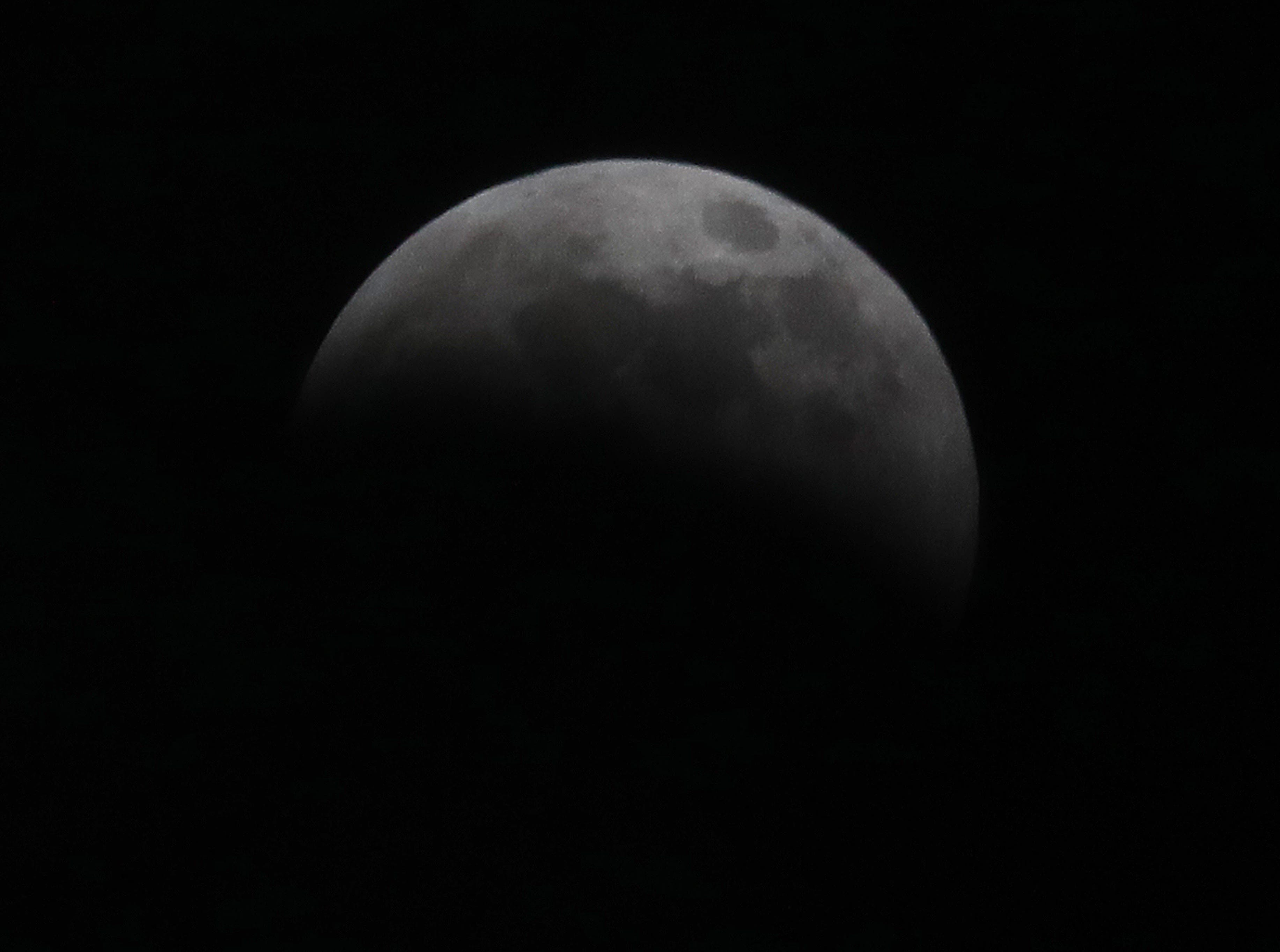 The moon is nearly covered in the shadow of the Earth during the lunar eclipse.