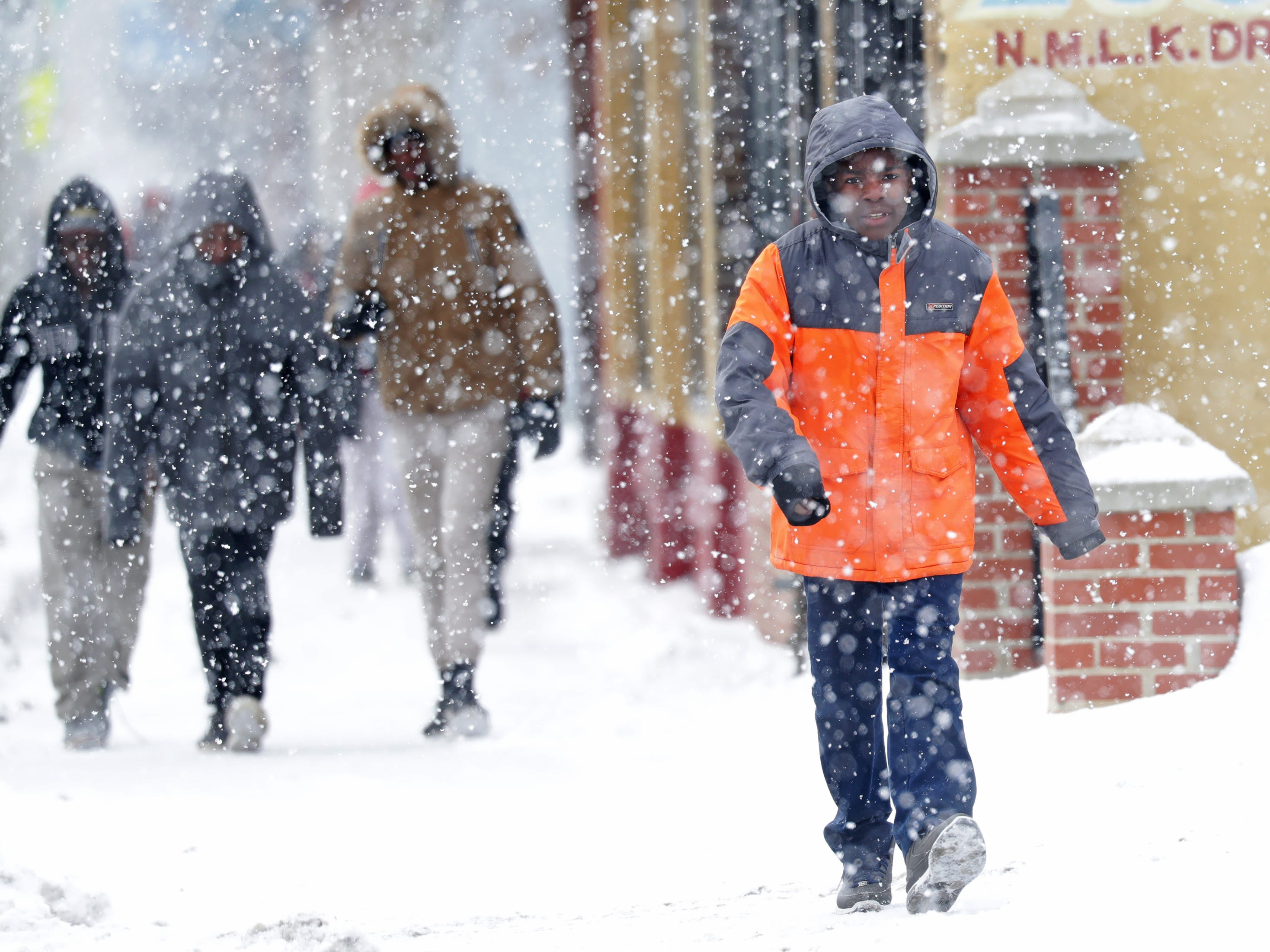 Clara Mohammed School student Sheikhnuur Abu, 12, walks with his class  through the falling snow to the Martin Luther King Library for a King event on West Locust Street in Milwaukee.
