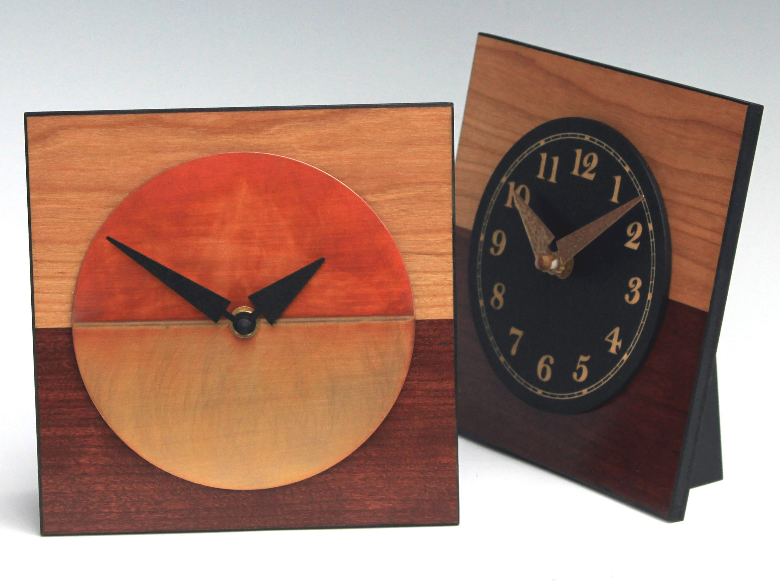 These two-tone desktop clocks ($75) from leonietime.com are cherry veneer with a copper face or painted, laser-etched wooden face.