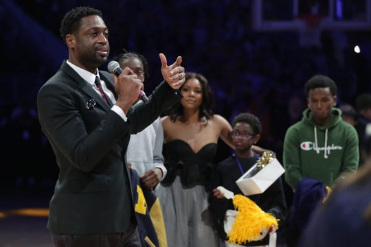 Former Marquette standout Famer Dwyane Wade speaks with his family behind as he is honored at halftime of the Golden Eagles' game against Providence on Sunday.