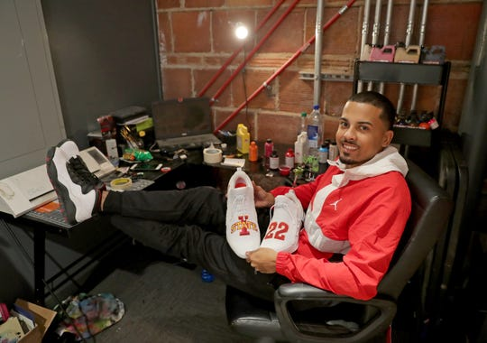 Noel Alvarado holds a pair of shoes he painted in his studio, None Above, in the Sherman Phoenix building in Milwaukee's Sherman Park neighborhood. He pained the shoes for Iowa State basketball player Tyrese Haliburton.