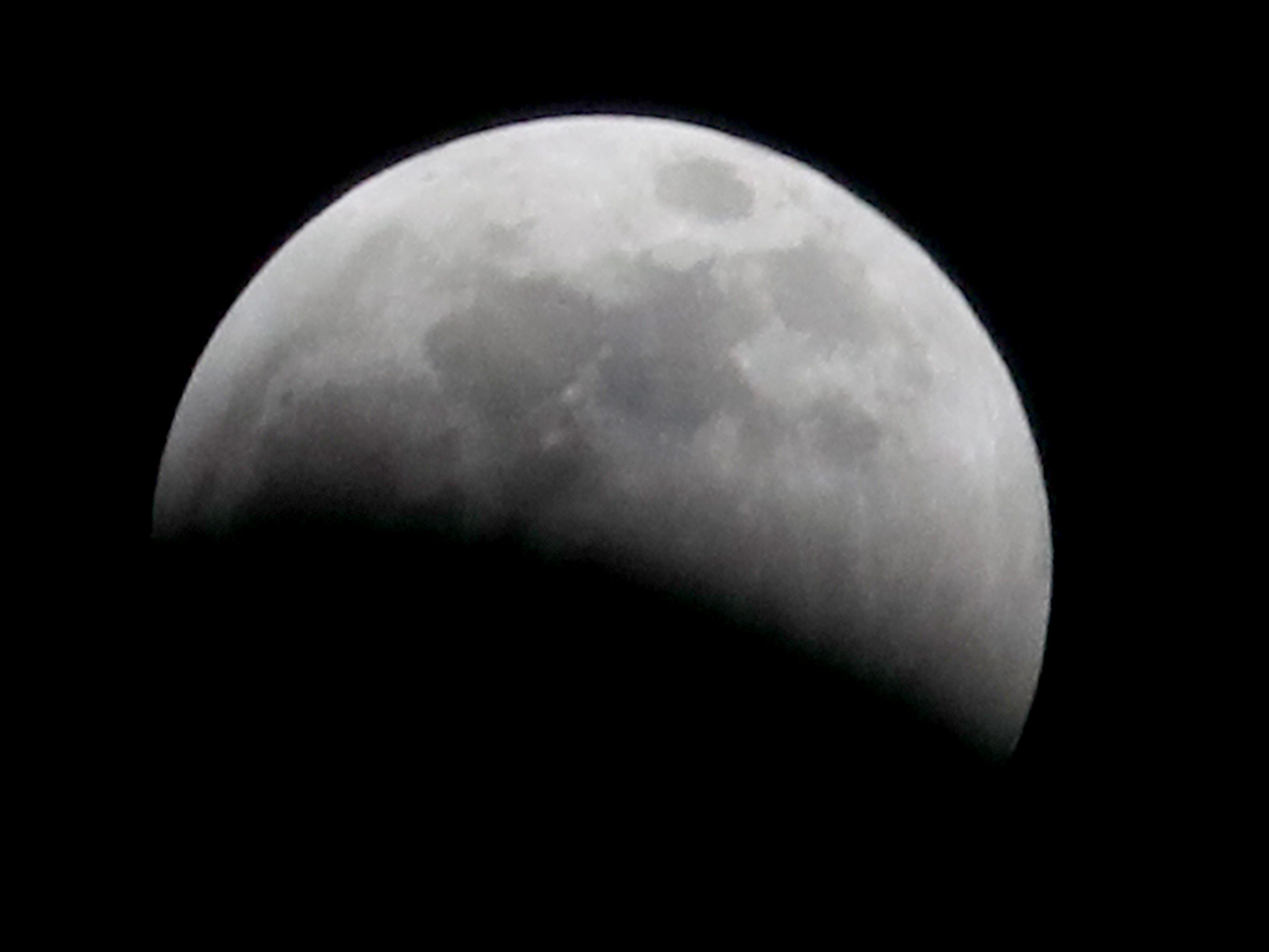 Nearly half the moon is covered before a total lunar eclipse.