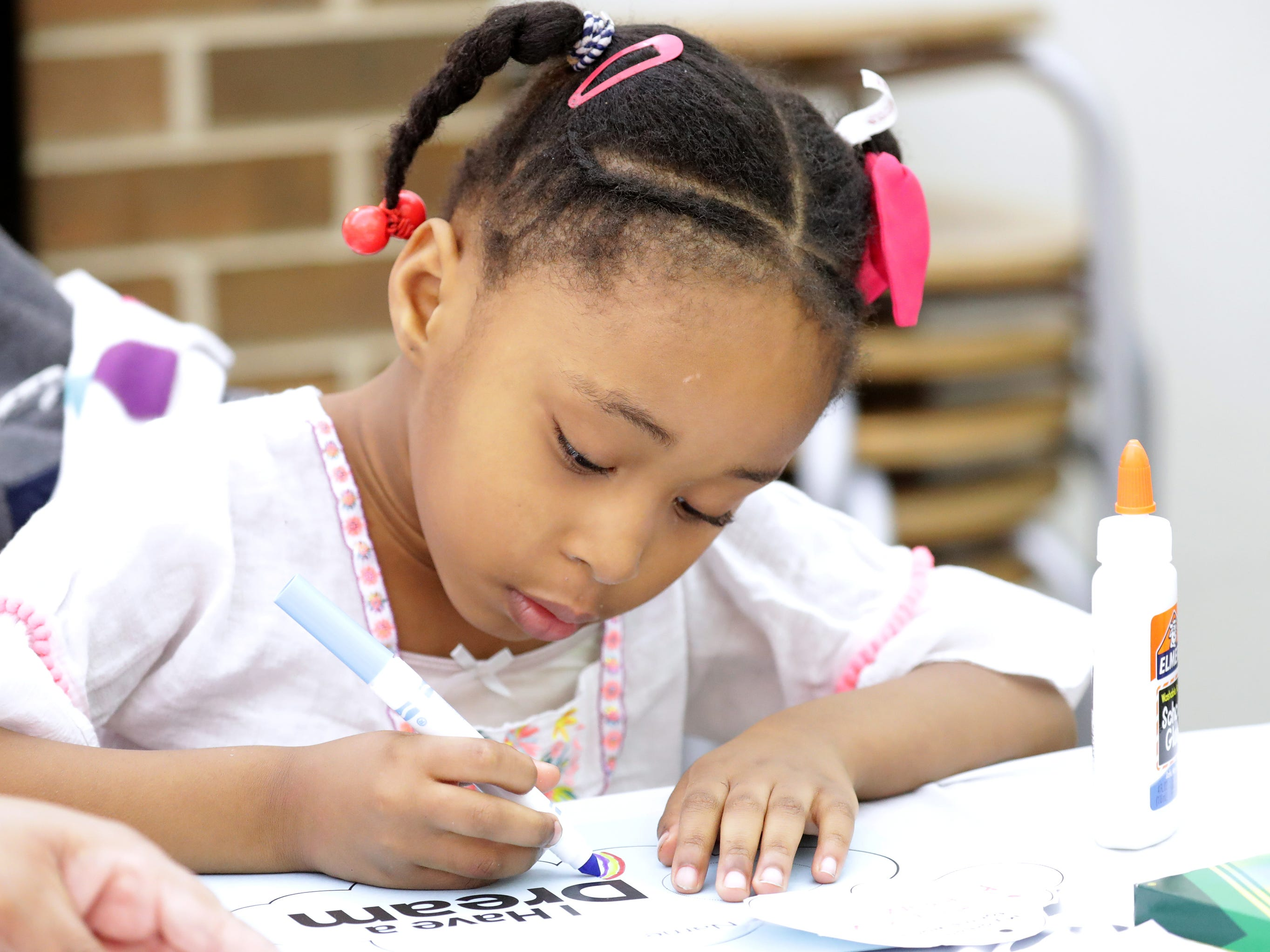 "Gia Deacon, 5, works on her ""I Have a Dream"" worksheet. She was with her mother, Shyla Deacon of Milwaukee, during a celebration at Martin Luther King Library."