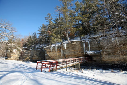 A footbridge crosses the west branch of the Pine River at the base of a sandstone rock formation at Pier County Park in Rockbridge.