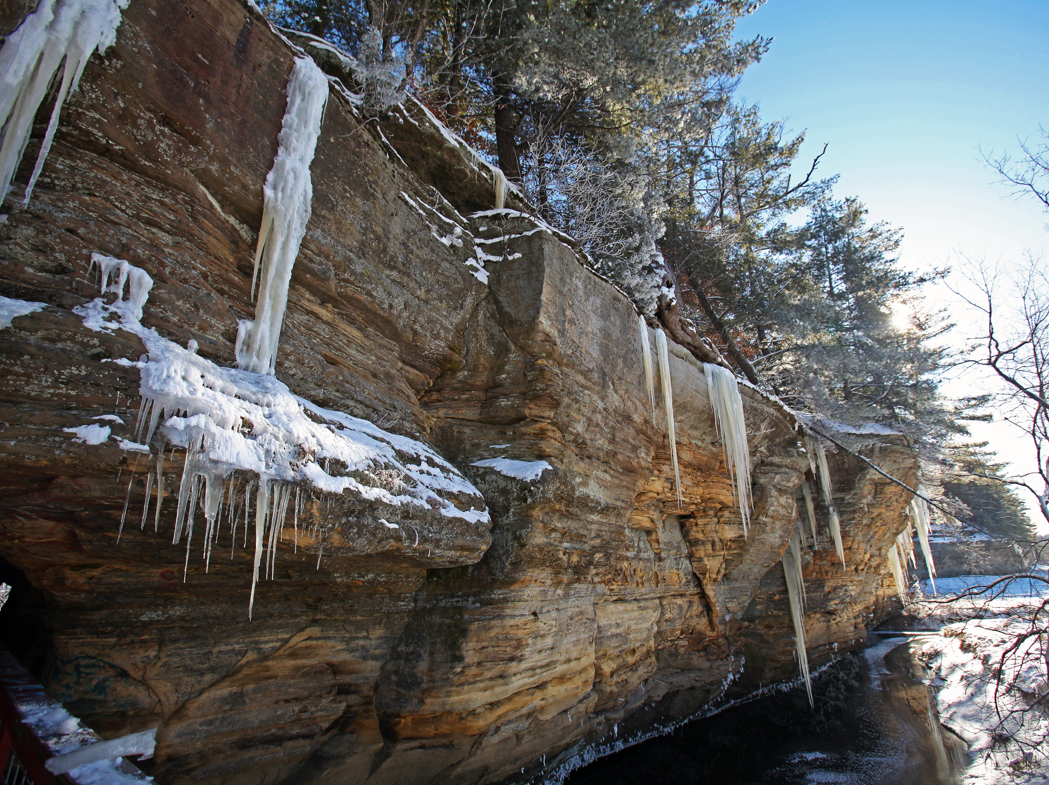 The west branch of the Pine River snakes along the edge of an icicle-laden rock formation at Pier County Park in Rockbridge.