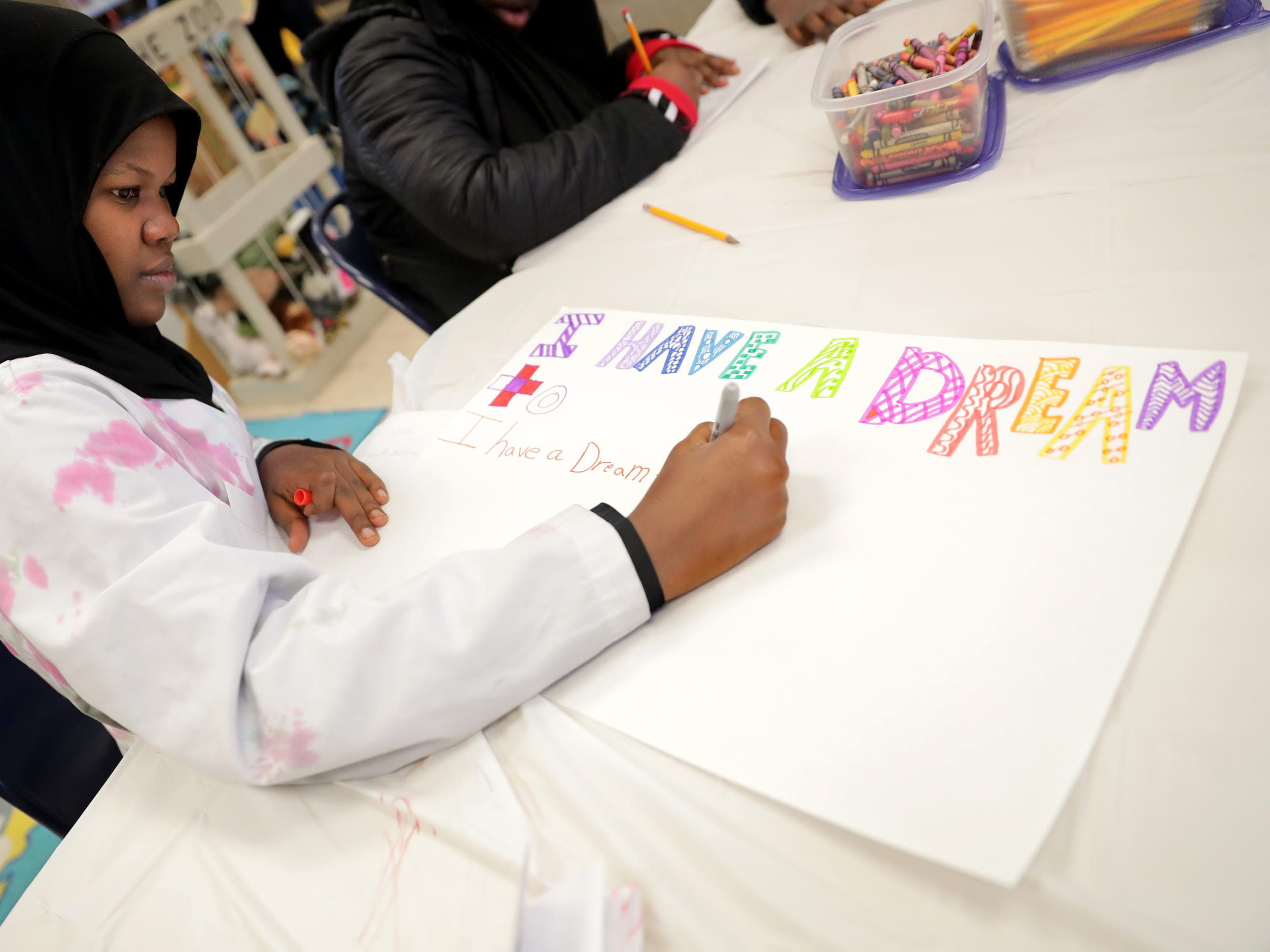 "Clara Mohammed School sixth-grader Mako Ali, 12, works on an ""I Have A Dream"" poster at Martin Luther King Library."