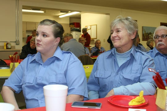 Henderson Volunteer Firefighters Ronni Bradford and Marita Standford listen to speaker and fellow volunteer Cheri Smith say a few words about former chief John Browning. Browning inadvertently joined the department in 1994 when he and his wife moved to Henderson. He went to the department to see if they needed someone to mow the grass around the building.