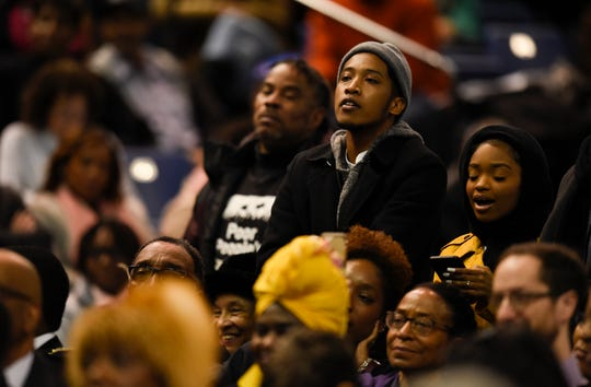 Justin Jones stands and listens to the Rev. William J. Barber at the Martin Luther King Jr. 30th Commemorative Convocation at Tennessee State University's Gentry Center on Jan. 21, 2019.