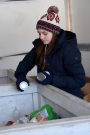"Granville High School junior Sarah Mortellaro, 17, sorts groceries in the back of a box truck from the Food Pantry Network of Licking County during the eighth annual ""Feed the Dream"" community food drive on Martin Luther King Jr. Day at Granville Ross' IGA. Volunteers collected donations of food and money during the day long event."