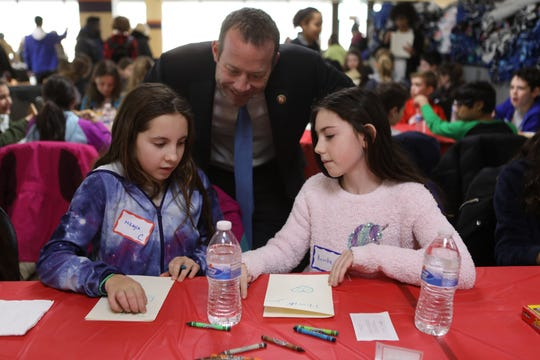 Rep. Josh Gottheimer speaks to Mikayla Sticco and Brooke Eialik, both 10, of Waldwick, as they make greeting cards for soldiers and veterans. The third annual MLK Day of Service for North Jersey students was held at Bergen Community College in Paramus on Monday, January 21, 2019.