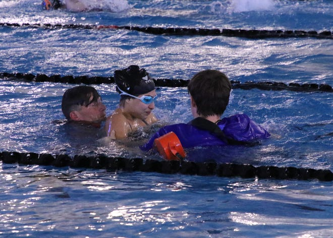 Carlsbad lifeguard Ross Meadors, right, and Artesia's Clayton McCall, right, help an Alamogordo swimmer who stopped swimming during the Jan. 19 meet in Carlsbad.