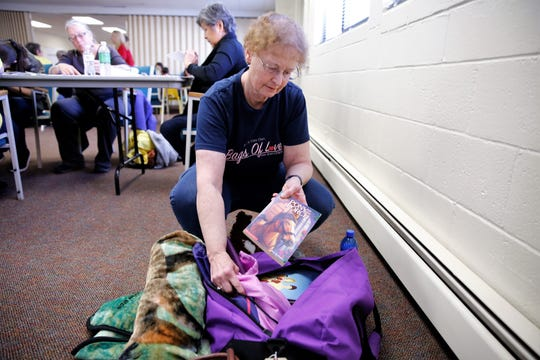 Wendy Bircher, a board member for the San Juan chapter of It's My Very Own, shows the contents of a Bag of Love, which is distributed to children who have been displaced from their homes, at First Presbyterian Church in Farmington on Monday. Volunteers at the Four Corners Martin Luther King Jr. Day of Service helped write notes for the bags.