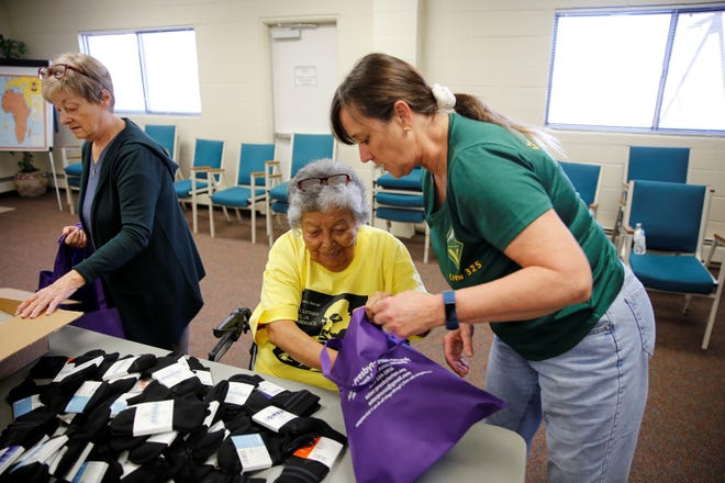 Volunteers Gwen Tedrow, left, Virginia Polacca, center, and Catherine Walker Grobler, right, assemble Blessing Bags for Aztec Presbyterian Church to distribute to people in need Monday as part of the Four Corners Martin Luther King Jr. Day of Service at the First Presbyterian Church in Farmington.
