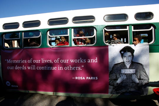 Children join Los Angeles County Metropolitan Transportation Authority employees as they ride a replica of the bus that civil rights leader Rosa Parks rode in Montgomery, Ala., when she was arrested in 1955, as they participate in the Martin Luther King Jr. Boulevard during the 34th annual Kingdom Day parade in Los Angeles on Monday, Jan. 21, 2019.