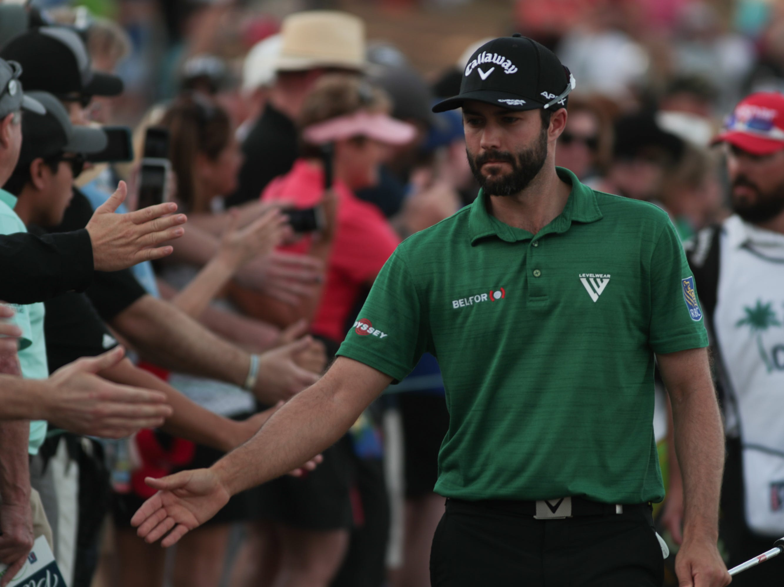 Adam Hadwin high fives fans as he walks to the 17th green of the 2019 Desert Classic, Sunday, January 20, 2019.