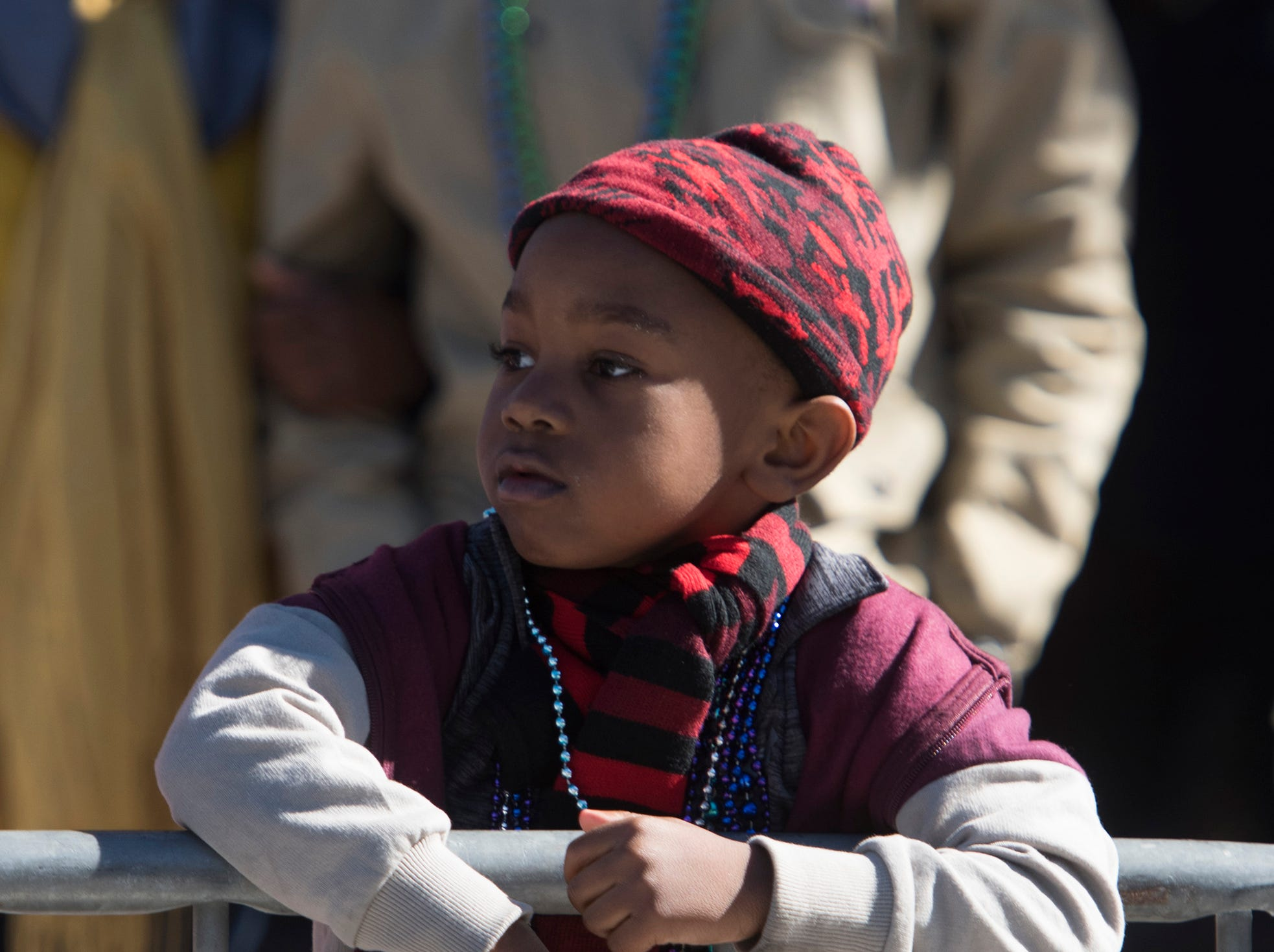 Jaden Dickens looks on as the Martin Luther King, Jr. parade moves closer to his location downtown Pensacola on Monday, Jan. 21, 2019.
