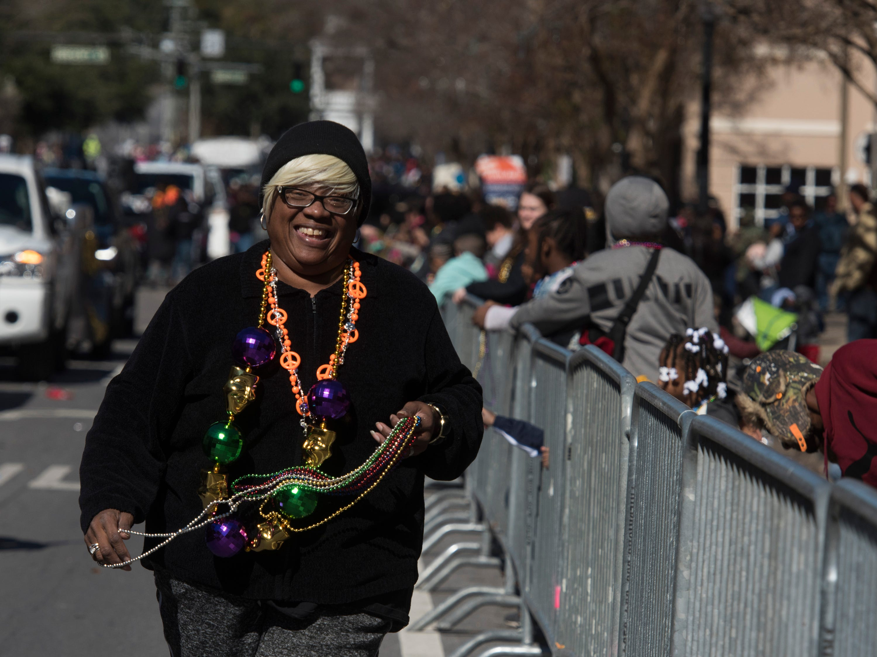 Wanda Baker passes out beads and trinkets with taking part in the annual Martin Luther King, Jr. parade in downtown Pensacola on Monday, Jan. 21, 2019.