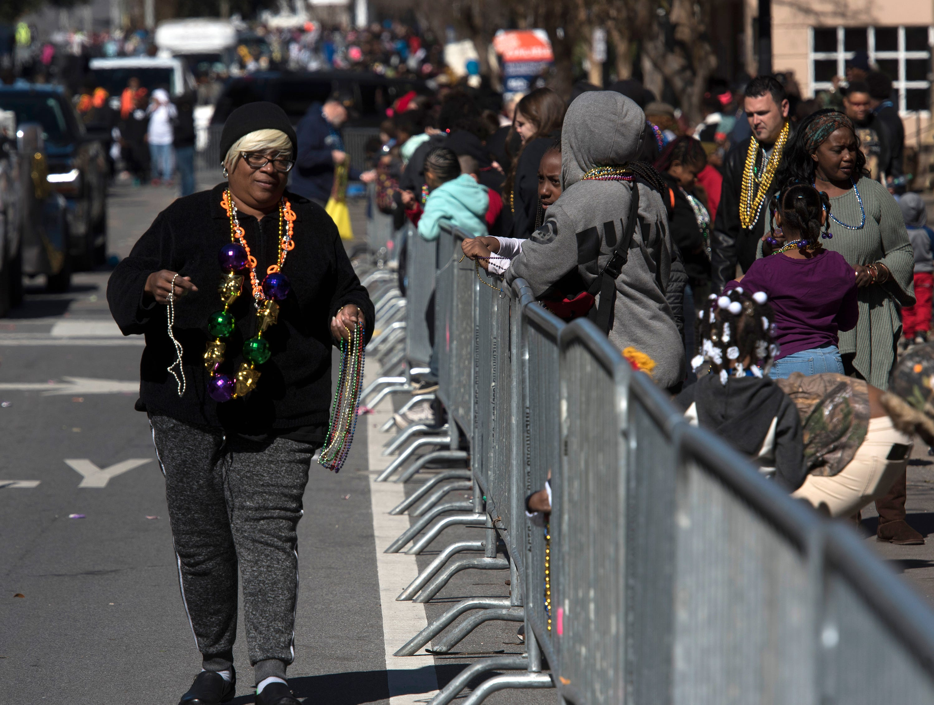 Wanda Baker passes out beads and trinkets while taking part in the annual Martin Luther King, Jr. parade in downtown Pensacola on Monday, Jan. 21, 2019.