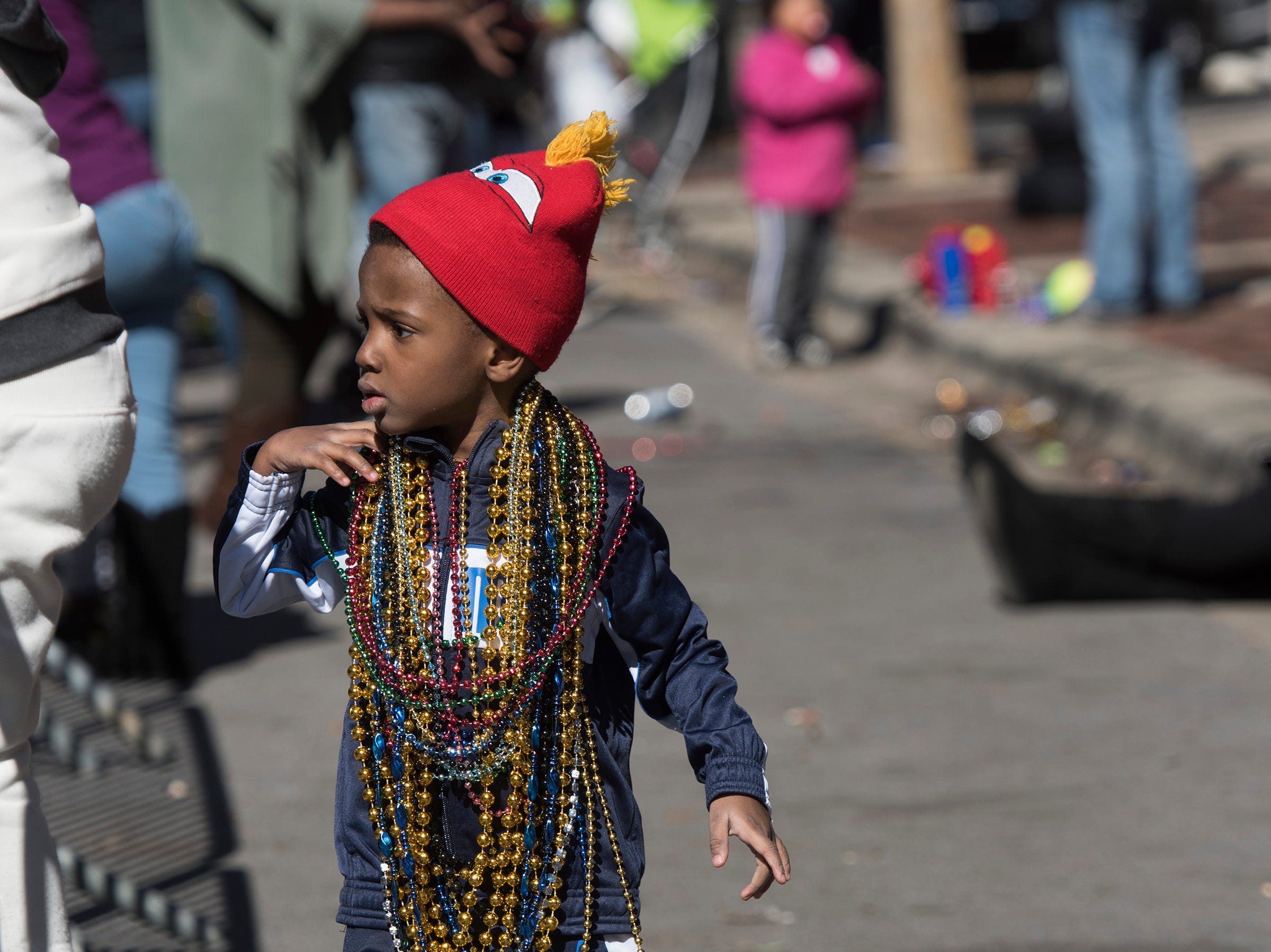 Jakayden Bryant, 4, gets loaded up with beads and other throws during the annual Martin Luther King, Jr., parade in downtown Pensacola on Monday, Jan.21, 2019.