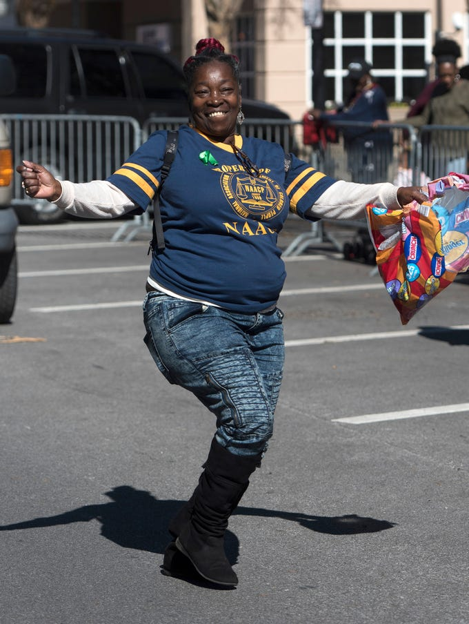 Linda Nobles, of the local chapter of the NAACP, entertains the crowd gathered in downtown Pensacola with dance and some throws during annual Martin Luther King, Jr parade on Monday, Jan. 21, 2019.
