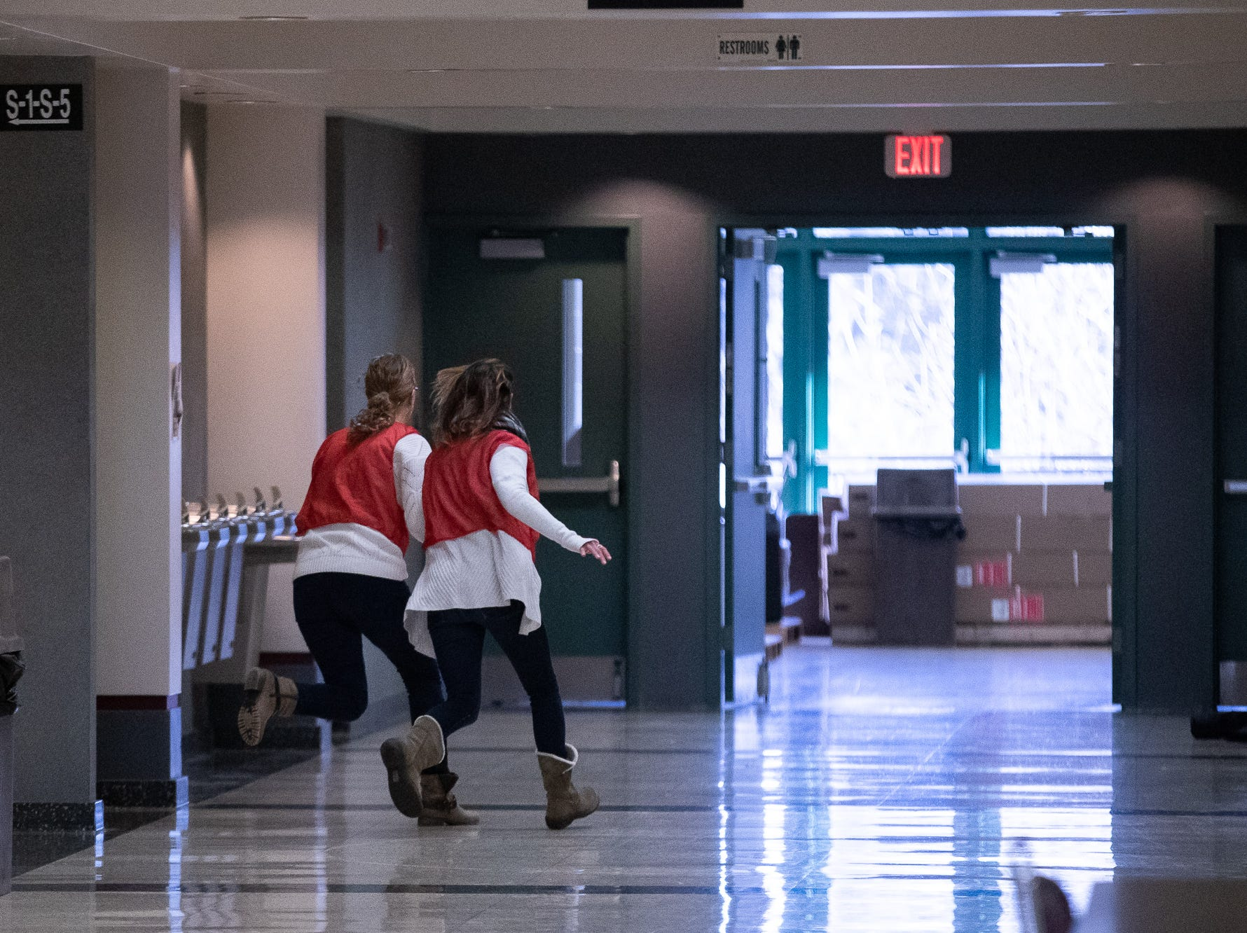School staff run for cover while they take part in an active shooter drill at South Western High School, Monday, Jan. 21, 2019, in Penn Township. The drill simulated multiple scenarios involving an active shooter, allowing school security and local law enforcement agencies a hands-on opportunity to drill on engaging an active shooter while also giving school staff experience with how real world scenarios could unfold.