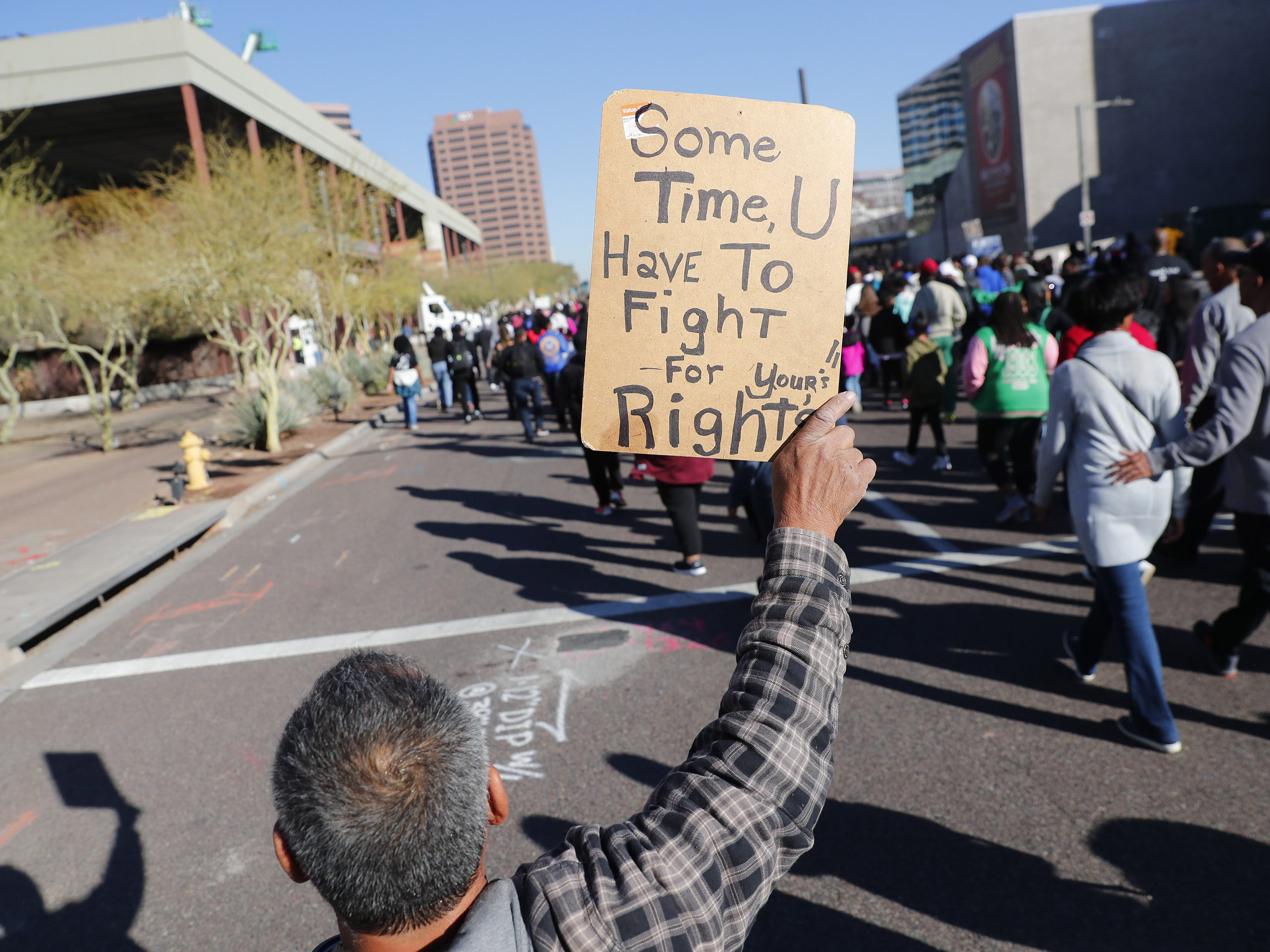 Robert Soria, 62 from Phoenix, holds a sign while marching with others honoring Dr. Martin Luther King in downtown Phoenix, Ariz. January 21, 2019. The march is symbolic of Dr. King's revolutionary 1968 march.