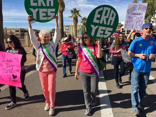 "At the Women's March in Phoenix, Beryl Braaten held high over her head with both hands a green-circle sign that said, ""ERA YES."""
