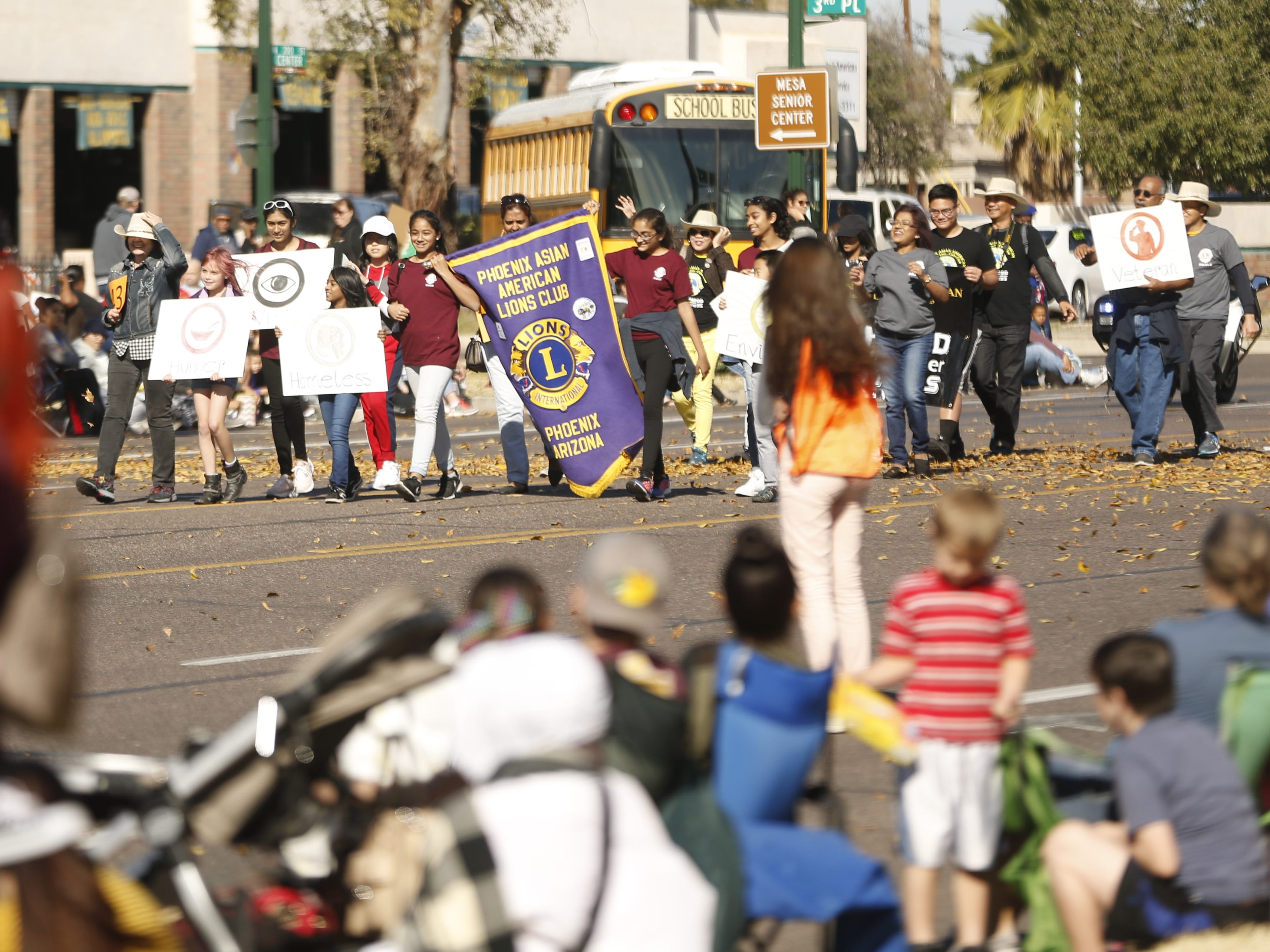 Phoenix Asian American Lion's Club waves at people on the side during the MLK Day Parade in Mesa, Ariz. on January 21, 2019.