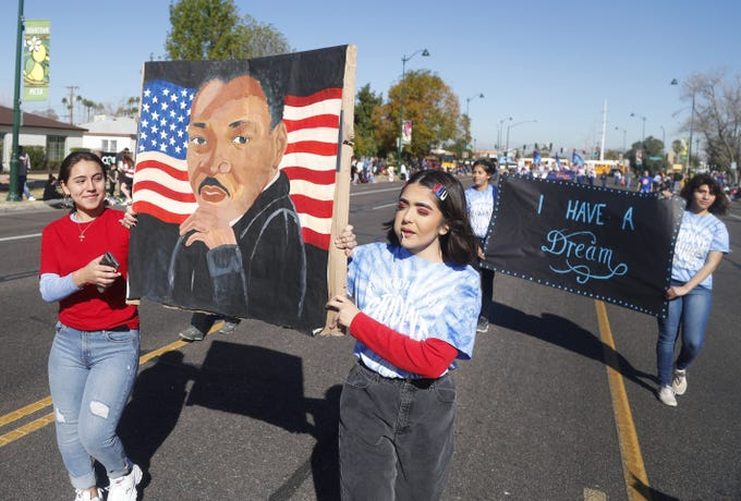 Westwood students Ana Torres (L) and Jamie Guzman carry a painting of Martin Luther King during the MLK Day Parade in Mesa, Ariz. on January 21, 2019.
