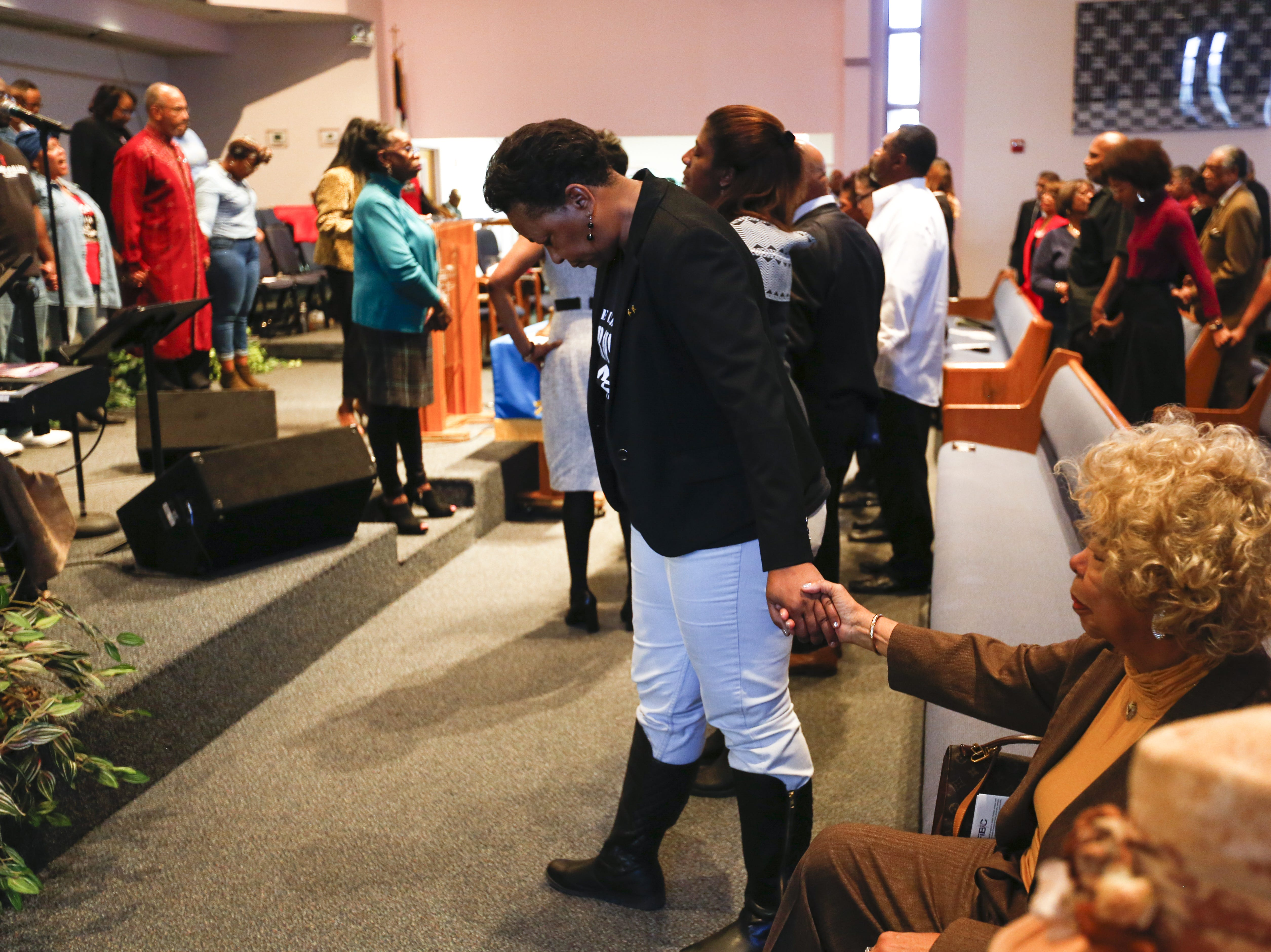 The congregation joins hands in prayer at First Institutional Baptist Church on Sunday, Jan. 20, 2019.