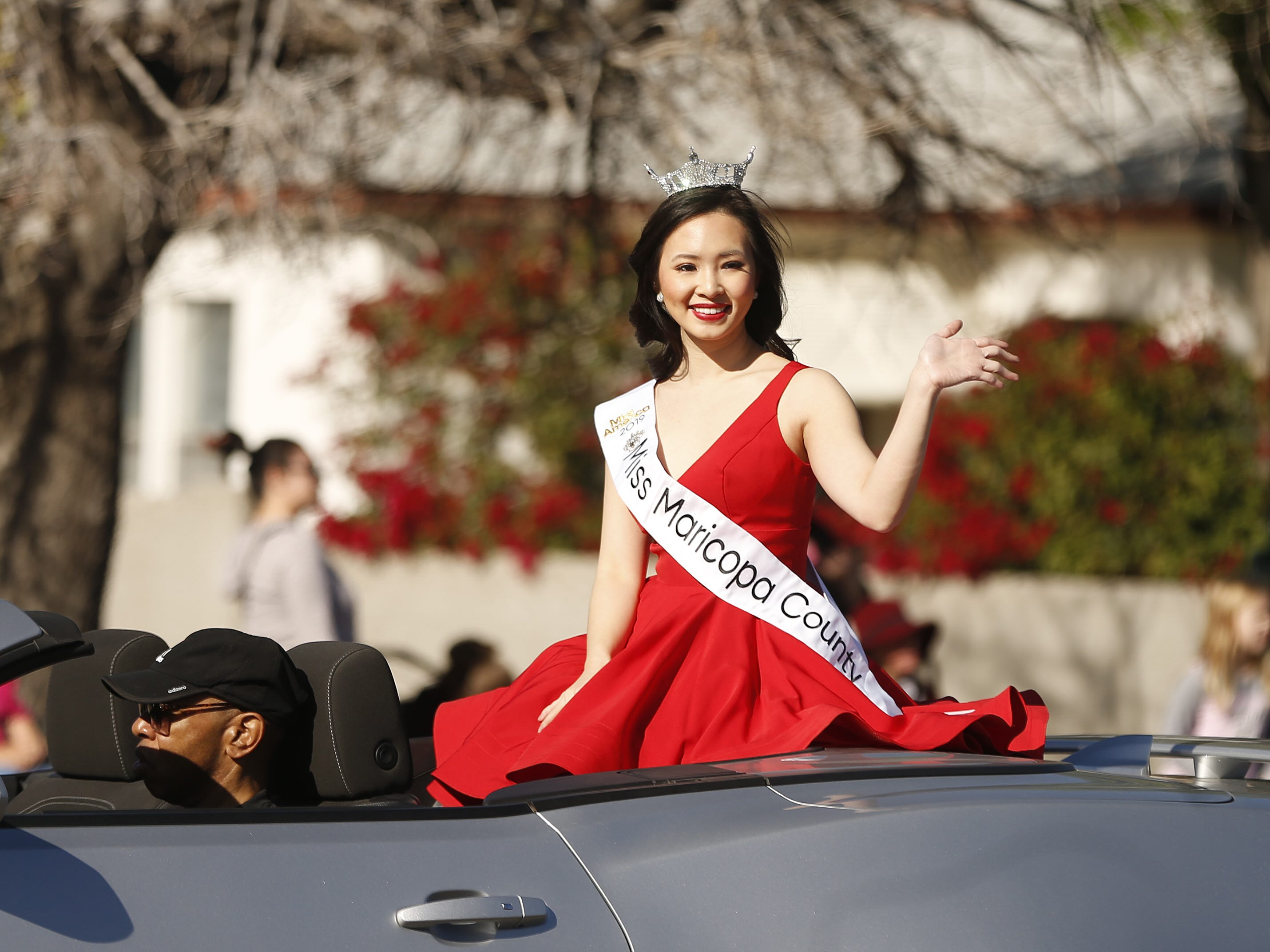 Miss Maricopa County's Laetitia Hua waves at people on the street during the MLK Day Parade in Mesa, Ariz. on January 21, 2019.