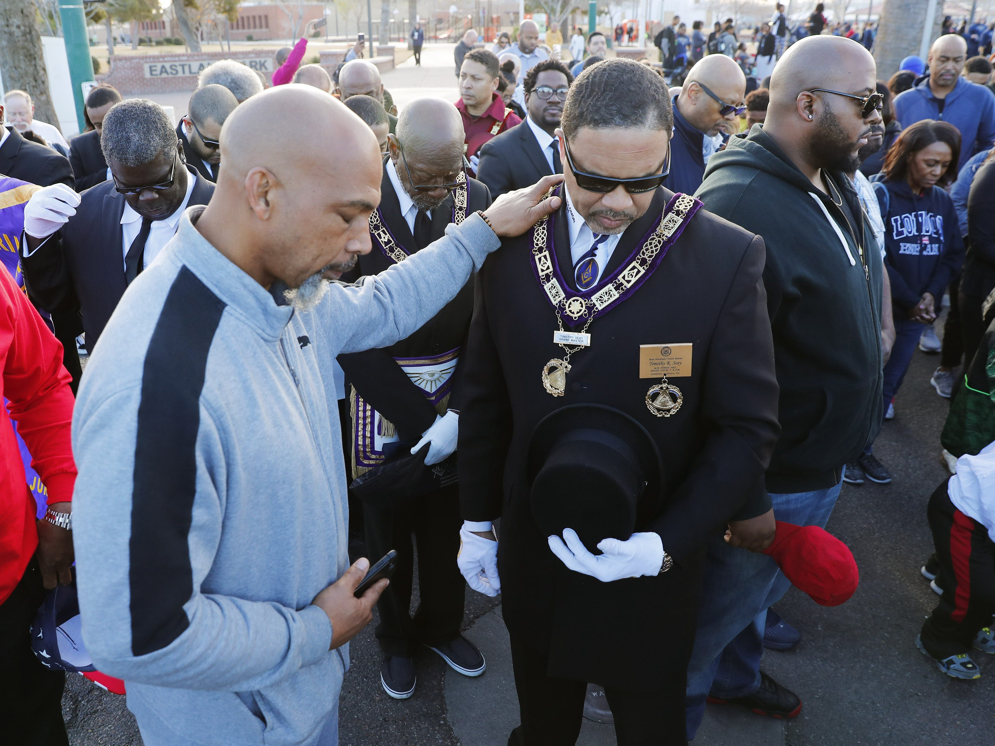 Kala Roy (left) and Timmothy Seay bow their heads in prayer before marching honoring Dr. Martin Luther King in downtown Phoenix, Ariz. January 21, 2019. The march is symbolic of Dr. King's revolutionary 1968 march.