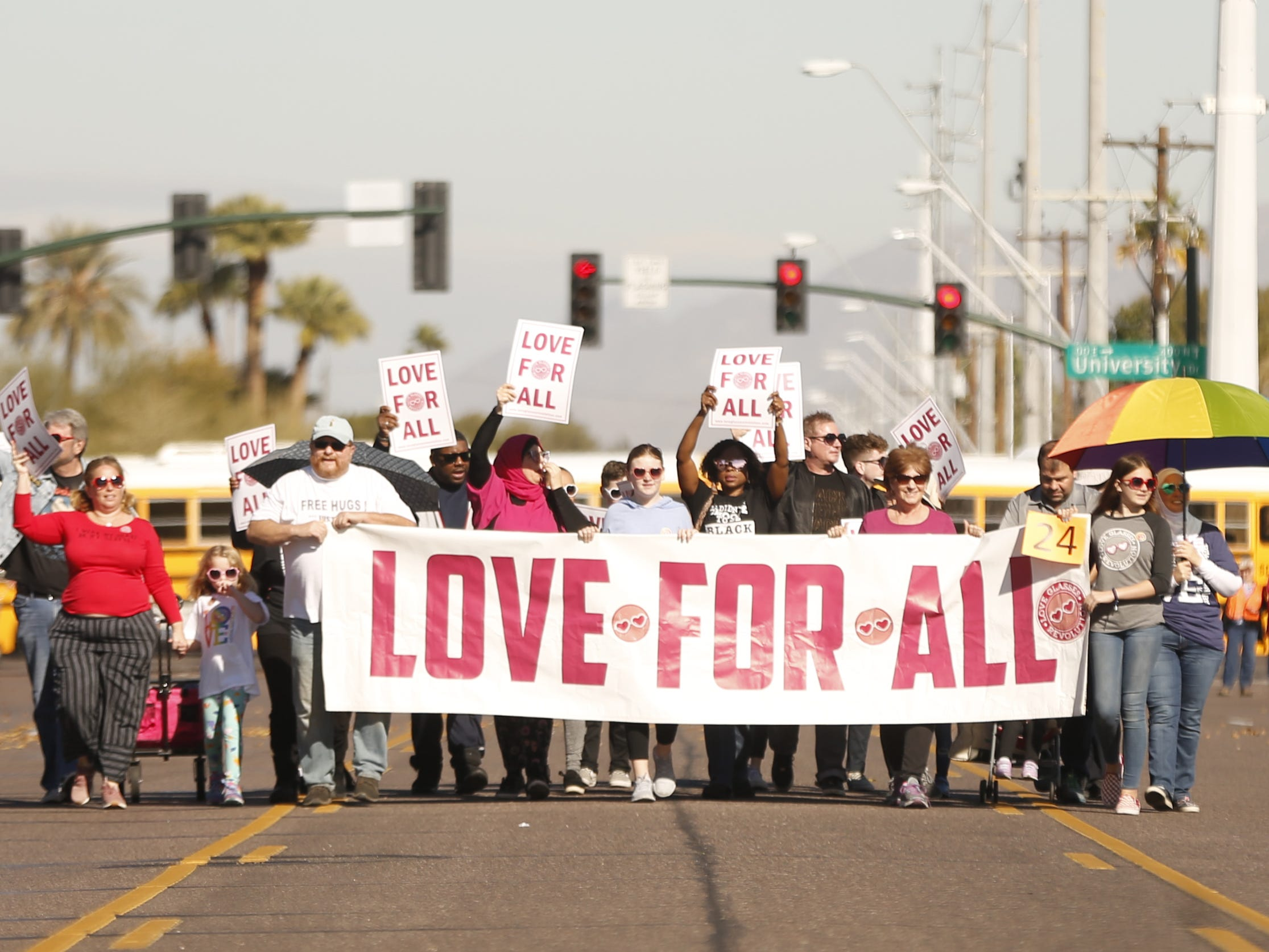 "People march with a ""Love for All"" banner during the MLK Day Parade in Mesa, Ariz. on January 21, 2019."