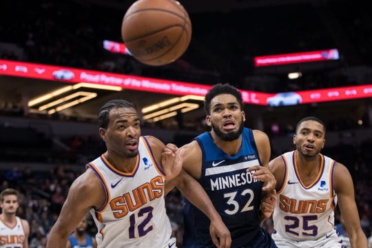 Jan 20, 2019; Minneapolis, MN, USA; Phoenix Suns forward T.J. Warren (12) and Minnesota Timberwolves center Karl-Anthony Towns (32) chase a loose ball in the fourth quarter at Target Center. Mandatory Credit: Brad Rempel-USA TODAY Sports
