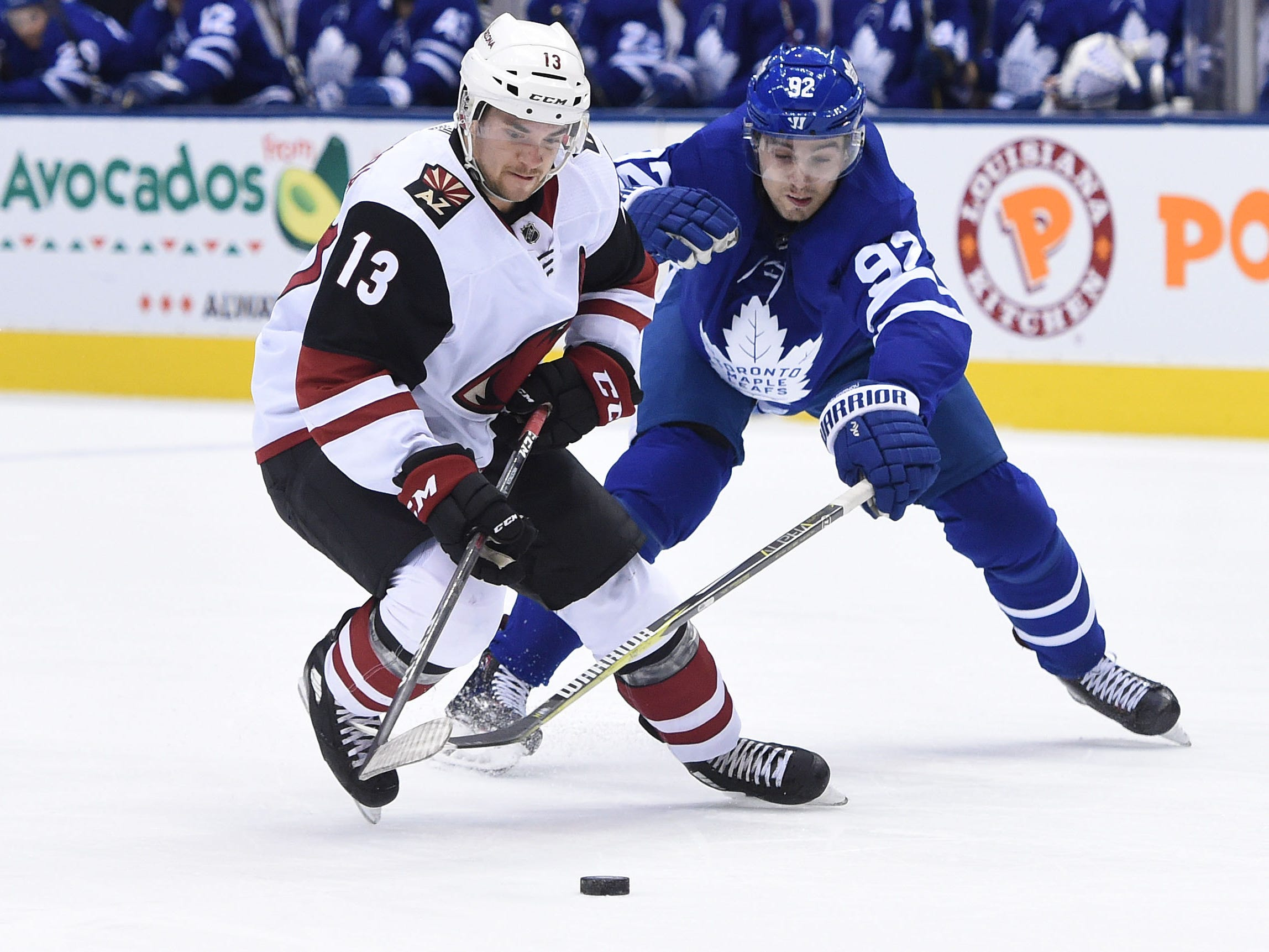 Jan 20, 2019: Arizona Coyotes forward Vinnie Hinostroza (13) and Toronto Maple Leafs defenceman Igor Ozhiganov (92) battle for the puck in the first period at Scotiabank Arena.