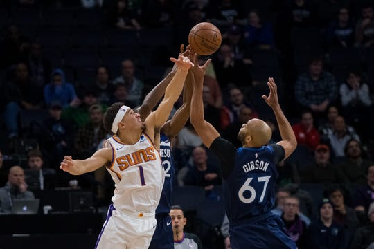 Jan 20, 2019; Minneapolis, MN, USA; Phoenix Suns guard Devin Booker (1) and Minnesota Timberwolves forward Taj Gibson (67) rebound in the fourth quarter at Target Center. Mandatory Credit: Brad Rempel-USA TODAY Sports