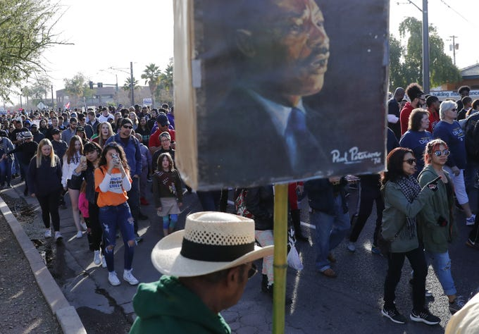 Milton Sampson carries a sign during a march honoring Dr. Martin Luther King in downtown Phoenix, Ariz. January 21, 2019. The march is symbolic of Dr. King's revolutionary 1968 march.